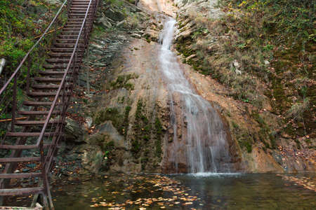 rise to the top: Metal staircase next to the waterfall, to rise to the top of the cliff Stock Photo