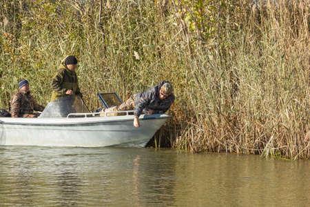 volga: Three fishermen catch fish on spinners in the Volga delta Stock Photo