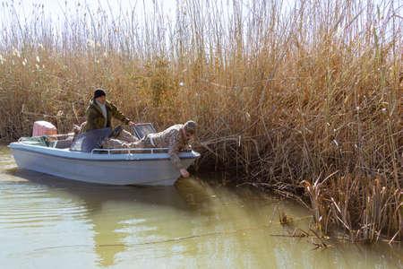 catch fish: Three fishermen catch fish on spinners in the Volga delta Stock Photo