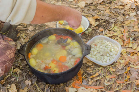 lays: Cook lays fish soup cooked over a campfire cups Stock Photo