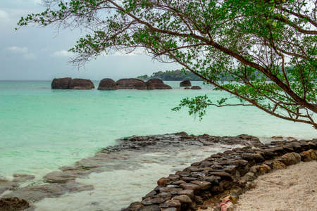 ocean and sea: Stone ridge next to a sandy beach on the background of a calm emerald sea