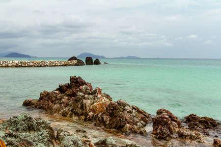 emerald stone: Stone ridge next to a sandy beach on the background of a calm emerald sea