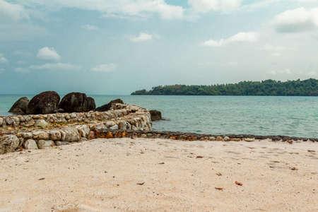 ridge of wave: Stone ridge next to a sandy beach on the background of a calm emerald sea