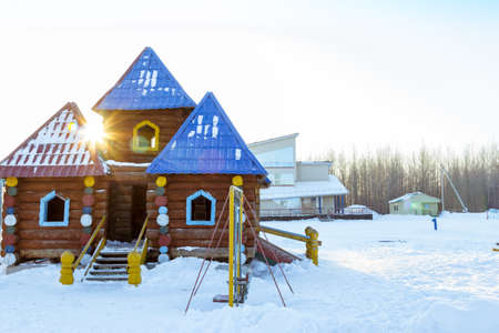 log cabin in snow: Childrens hut made in the form of a log log Stock Photo