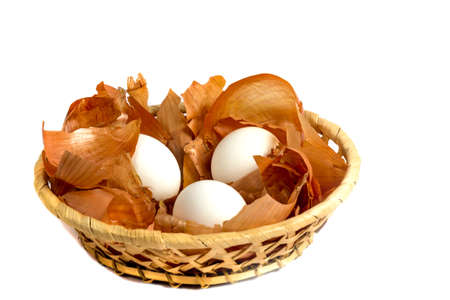 onion peel: Three eggs in a wicker basket with straw onion peel on a white background Stock Photo