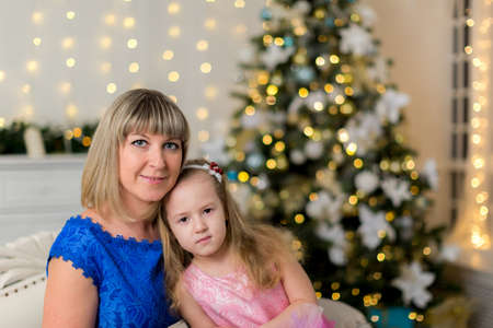 Mom and daughter on the background of a decorated Christmas tree
