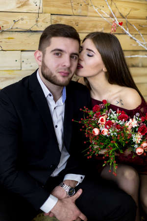 A young man in a black suit and a girl with a bouquet of flowers on a wooden wall background