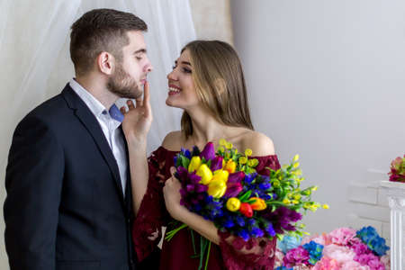 Loving and happy young man with a girl on a white background with red flowers
