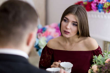 A guy and a girl are chatting at the table with a cup of coffee