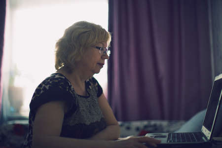 An elderly woman enthusiastically working at the computer