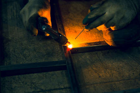 The welder lights the arc and begins to weld the metal structure of stainless steel Reklamní fotografie