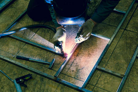 The welder lights the arc and begins to weld the metal structure of stainless steel 스톡 콘텐츠