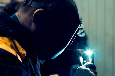 A welder welds a metal piece and sparks from welding fly in different directions