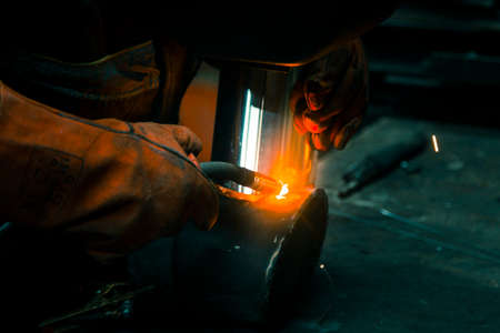 The welder lights the arc and begins to weld the metal structure of stainless steel 版權商用圖片