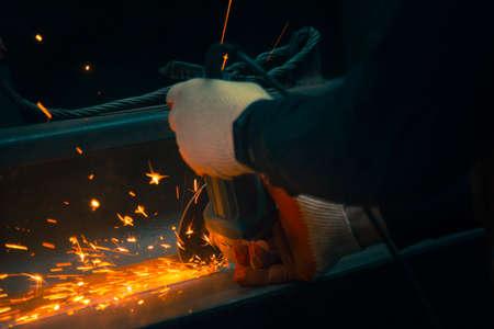 The hands of a mechanic grinder in gloves at work Reklamní fotografie