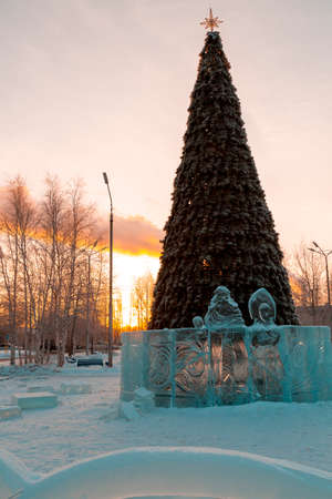 Santa Claus and snow Maiden cut out of ice on the background of the Christmas tree in the rays of the setting sun Stock fotó