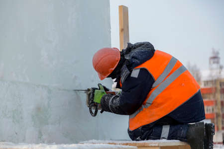 Workman assembler in a protective helmet with a chainsaw in his hands cuts the ice block