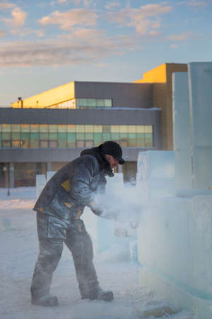 The sculptor cuts ice contours from ice with a chainsaw for Christmas