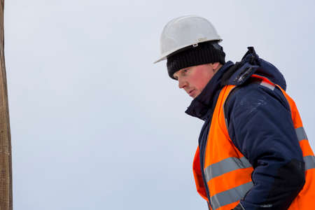 Portrait of an assembler worker in a jacket with a hood and a white helmet at unloading ice plates Stock Photo
