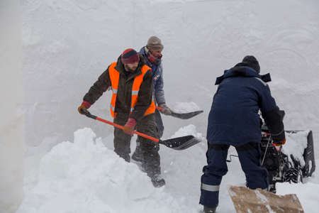 Workers remove snow in a blizzard using a snowplow