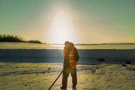 Portrait of a worker in an orange reflective vest snow shoveling on a river ice
