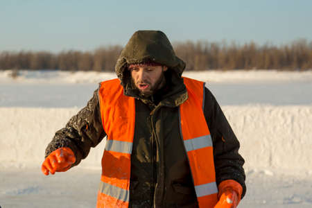 The average plan of a worker with a hood on his head in an orange reflective vest