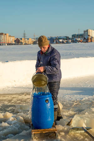 A worker in a blue jacket and a brown knitted hat on his head pours a bucket of water into the barrel of the ice-hole