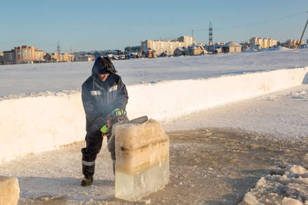 Worker in a blue jacket with a hood cuts a chainsaw ice block out of the hole Imagens