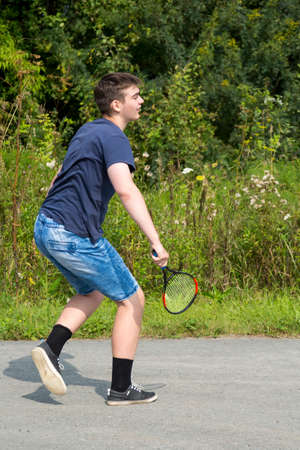 Teen boy with a racket in hand plays badminton 스톡 콘텐츠