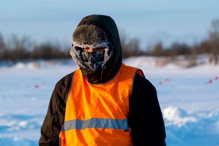 Der durchschnittliche Plan des Arbeiters im Schutzanzug, Eis eines gefrorenen Reservoirs, dessen Gesicht mit Raureif bedeckt war. Standard-Bild