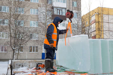 Portrait of an assembler worker in an orange reflective vest and a helmet unloading ice panels