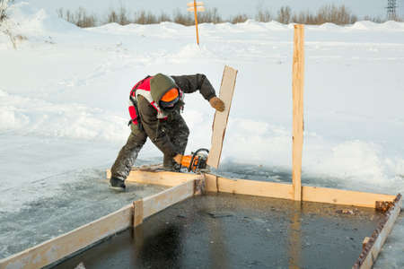 An installer in an orange reflective vest, cuts a chainsaw into a formwork near an ice hole