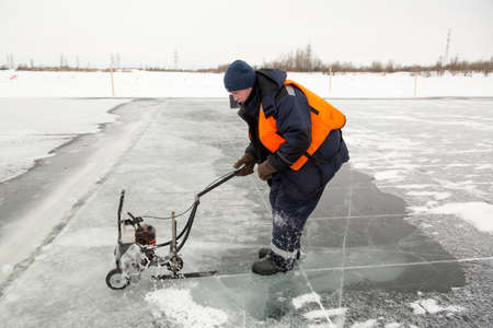 An ice sawyer in an orange life jacket carves ice panels on the ice of a frozen pond