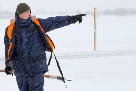 Worker on the ice of a frozen lake with bogr in his hand on ice mining Stock fotó
