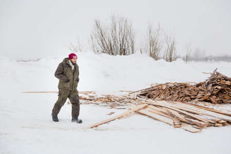 An installer in green winter workwear walks along an assembly site against a background of stacked boards