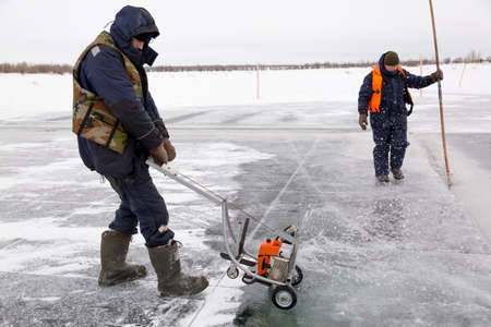 An ice sawyer in a protective life jacket, cuts out ice panels on the ice of a frozen reservoir