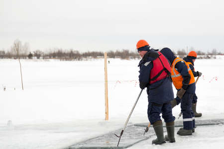 Installers in life jackets rafting ice panels to the lane with the beograms Stock Photo
