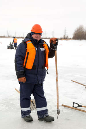 Worker on the ice of a frozen lake with bogr in his hand on ice mining