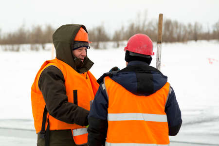 Portrait of an installer in a green jacket and an orange reflective vest with a hood on his head