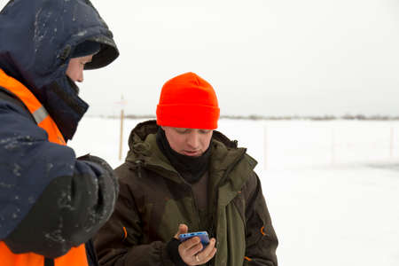 A man in a winter uniform and a red knitted hat on the ice of a frozen pond talking on a cell phone