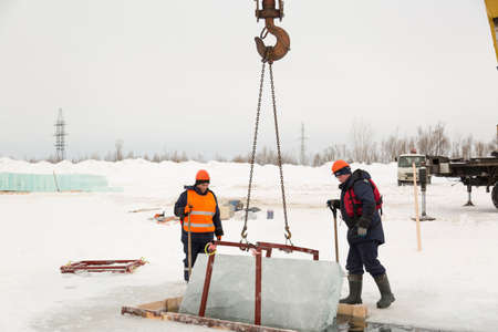 Workers observe the lifting of ice plates with a lane crane using metal frames