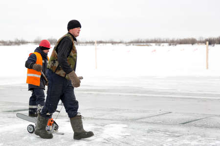 A man in a winter uniform is walking on the ice of a frozen pond with a machine for cutting ice