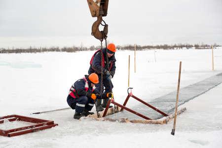 Slingers start a metal frame under the ice blocks in the lane Standard-Bild
