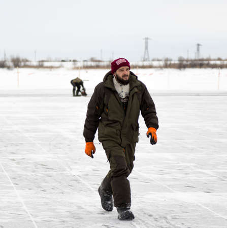 Worker in a jacket with a hood and a woolen knitted hat on the ice of a pond