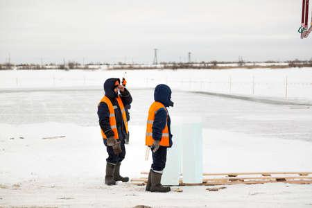 Worker slingers in orange reflective vests and helmets ship ice panels