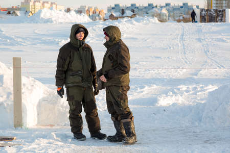 Installers in winter overalls are talking on the ice of a frozen river
