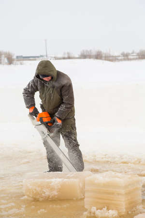 An ice sawyer cuts a font for Epiphany with a chainsaw in a frozen river
