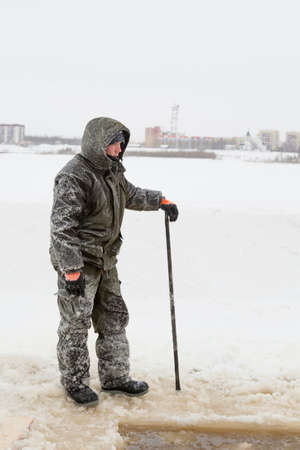 An installer in a green jacket with a hood on his head on the ice of a frozen river Stock Photo