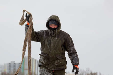 Worker in a green winter suit with a hood on his head with slings in his hand