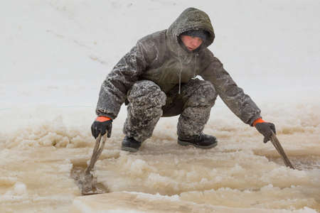 A worker in a green winter suit with a hood on his head makes slings under an ice block on the ice of a frozen river